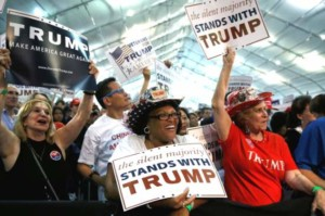 Several Supportes of President Trump at a rally and cheering wildly, they all look very excited and happy.