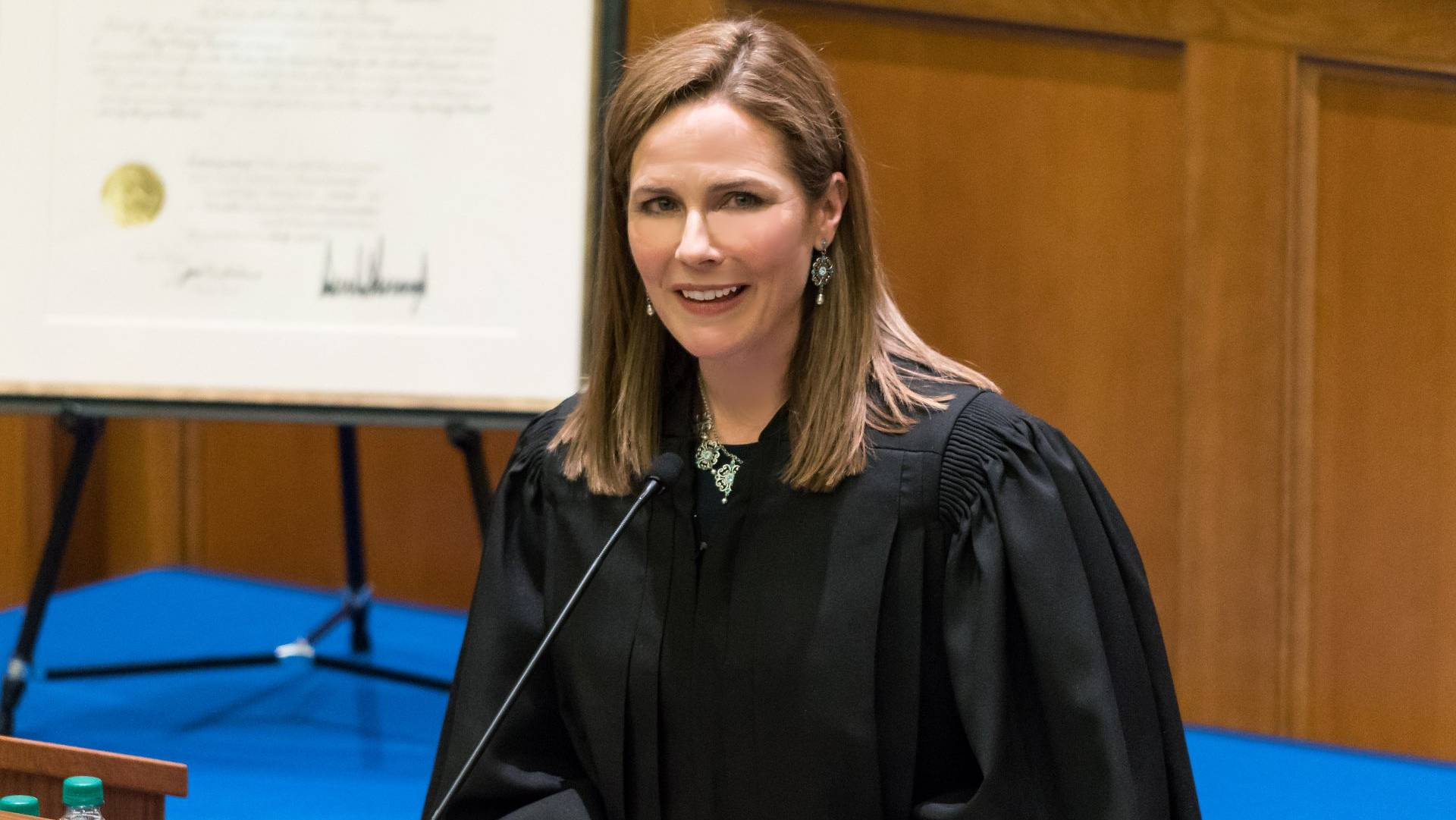 An image of Supreme Court Justice Judge Amy Coney Barrett speaking in her robe in what look like aclassroom setting, she is smiling, her hair islite brown and blonde highlights, she is an attractive woman.