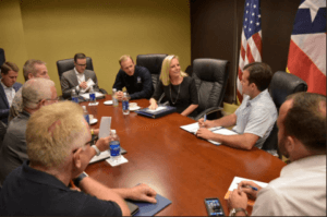 Secretary Nielsen attends meeting with FEMA employees working at the Joint Field Office they are all seated around a large conference table and everyone is looking at a smiling Secretary Nielsen