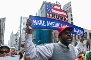 "An image of a black man with a red trump hat on and wearing a white shirt with a grey sweater and neck tie, he is marching in a rally to support president trump, he is holding a big sign above his the that sats ""Trump Make America Great Again""."