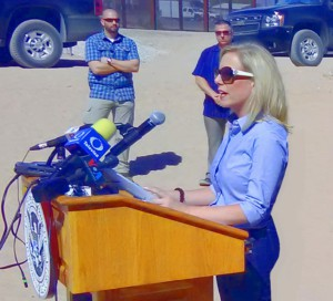 an image of kirstjen nielsen at a podium outside near the mexican border it's a very sunny day madam secretary's looks golden in the sun, she is wearing sun glasses and looks really hot