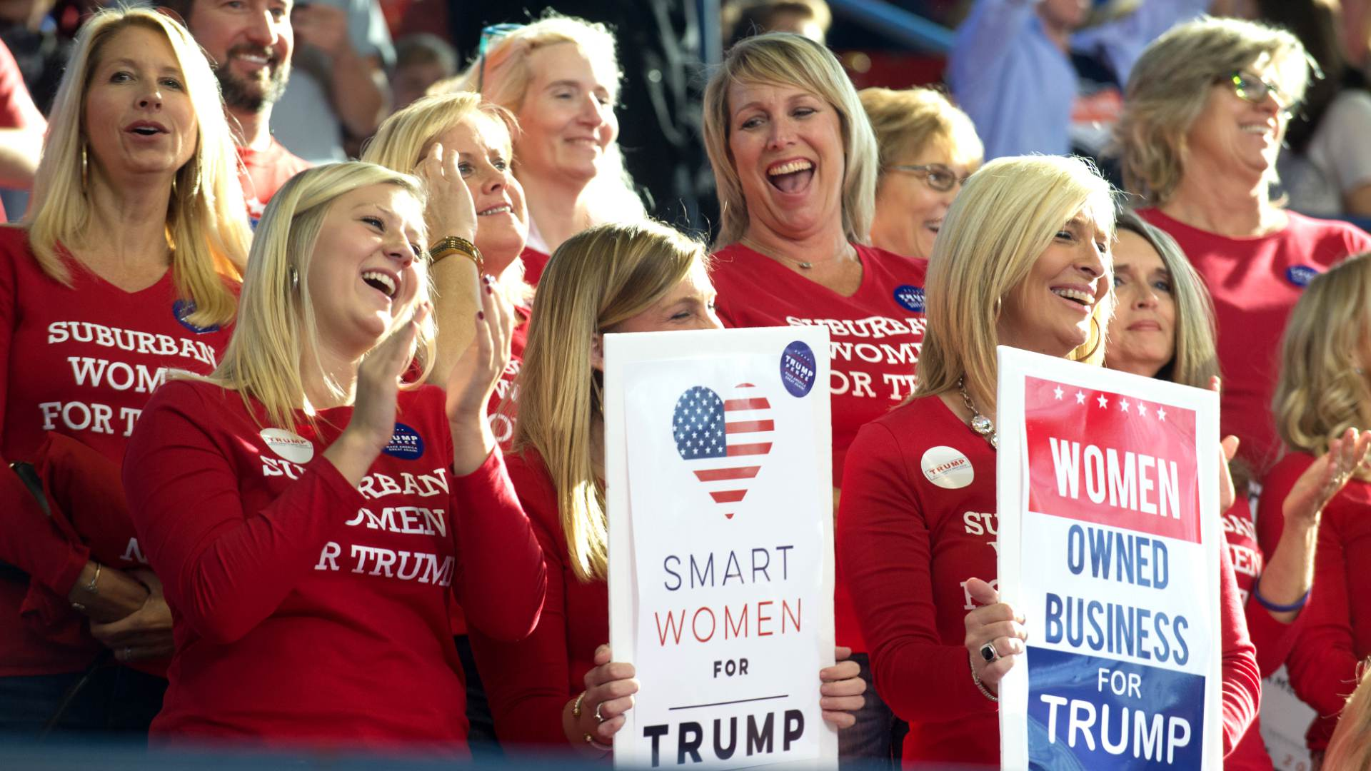 An image of a dozen or more Women Trump supporters they all have a red t-shirt on that says suburban women for Trump. They are at a rally and they look very happy clapping their hands and yelling