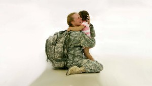 image of a woman coming home she is dresses in her army fatigues and she went to her knees to hug her child she is weeping hard