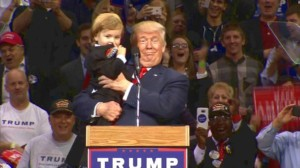 An image of president trump at a rally and he is holding a boy around the age of 2 with a suit on and his hair styled like the president, he is smiling and looking towards the camera and everyone else is laughing and smiling.