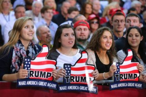 "An image of 4 young women trump supporters the look to be in their 20's each is smiling and looking up at President Trump on the stage, each woman is holding a sign in the shape of a thumbs up hand with a U.S. flag background and the signs read ""Trump Make America Great Again"""