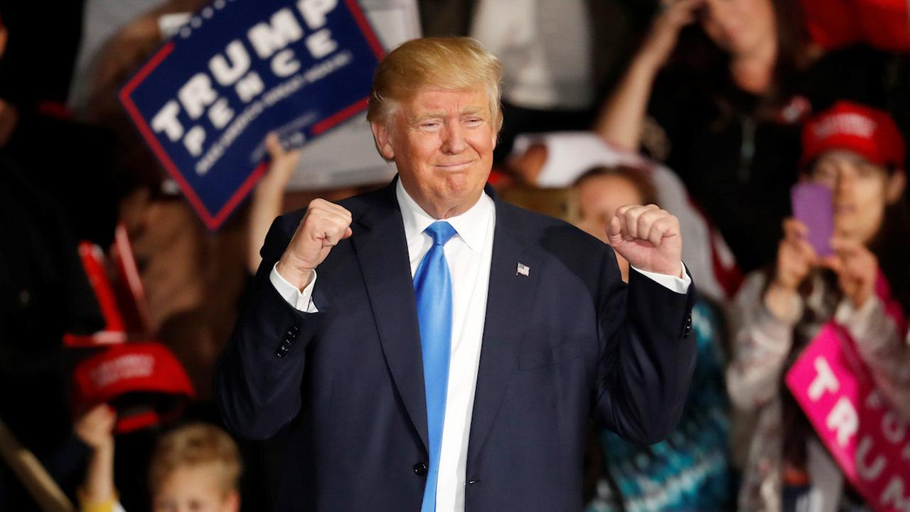 An image of president trump at a rally, wearing a blue suit and red tie, with his fists up in victory.