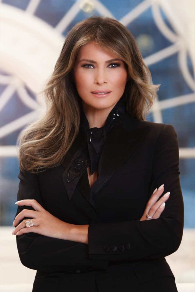 an image of First Lady Melania Trump she is facing the camera and smiling she has long dark hair and a beautiful face, she is wearing a dark purple jacket with a lighter purple scarf, she look great.