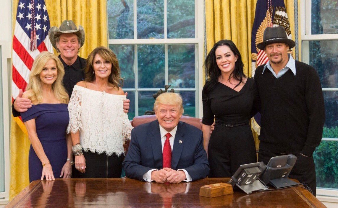 An Image Of Ted Nugent His Wife, Sarah Palin, Kid Rock and His Wife visit President Trump in the Oval Office, they are all standing to the back of president trump who is seated at his desk, all are smailing and look happy.