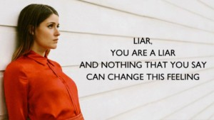 "an image of a attractive woman leaning against a wall and the caption reads ""Liar, you are a liar and nothing you say can change this feeling"""