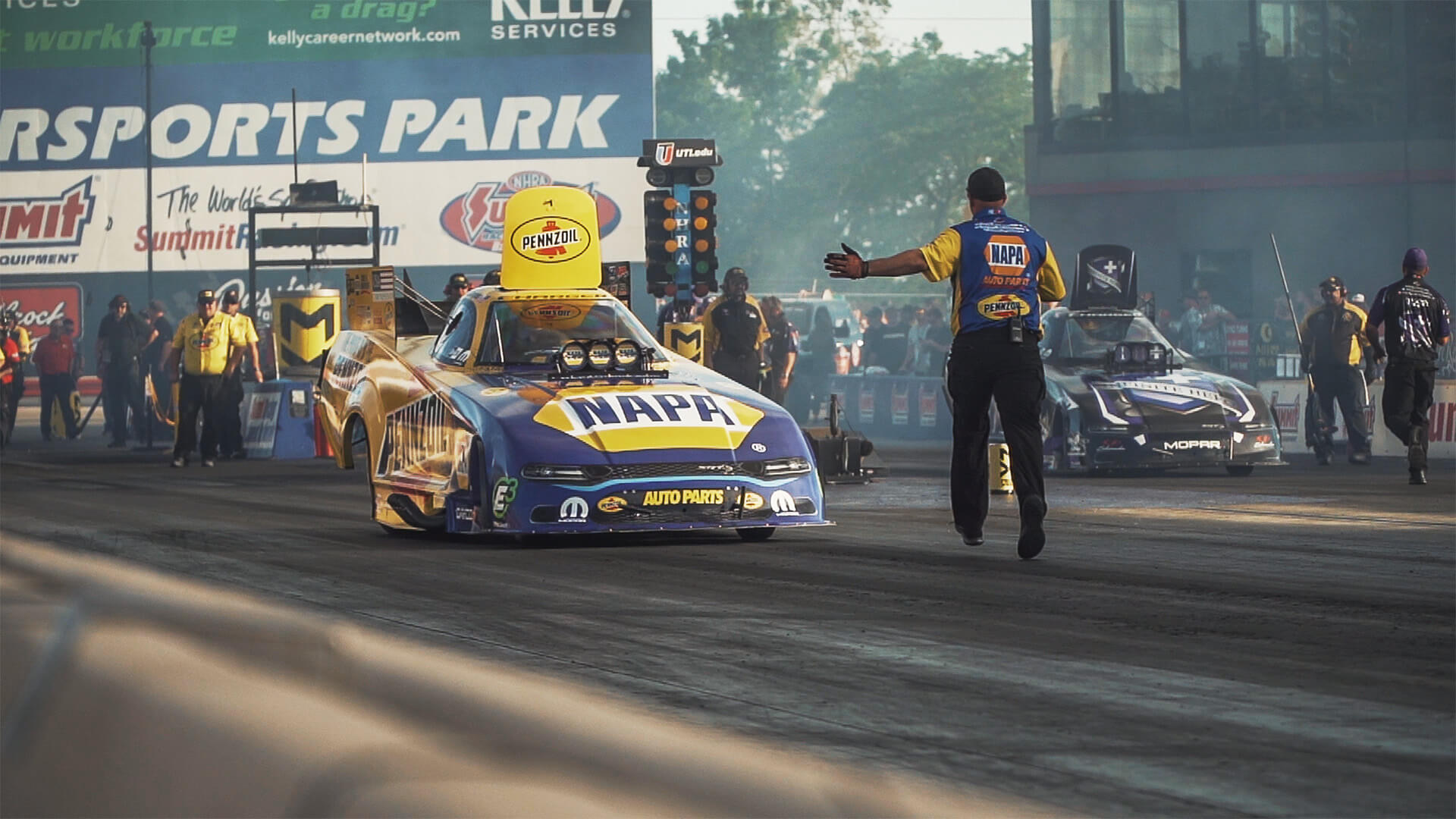 Crew members help guide Ron Capps and Jack Beckman back towards the starting line at the 2019 Summit Racing Equipment NHRA Nationals.