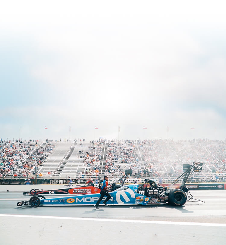 Leah Pruett and Shawn Reed back up their Top Fuel Dragsters during the first round of eliminations at the 2019 NHRA U.S. Nationals.