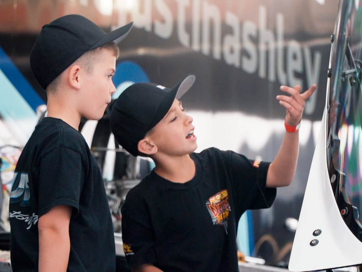Kids check out the canopy on Justin Ashley's NHRA Top Fuel Dragster.
