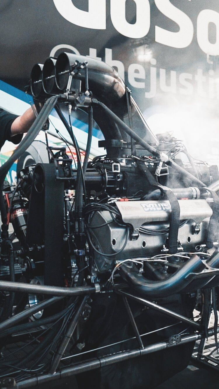 Crew members on Justin Ashley's Top Fuel Dragster make adjustments during a pre-run warmup in the pits at the 2019 NHRA World Finals.