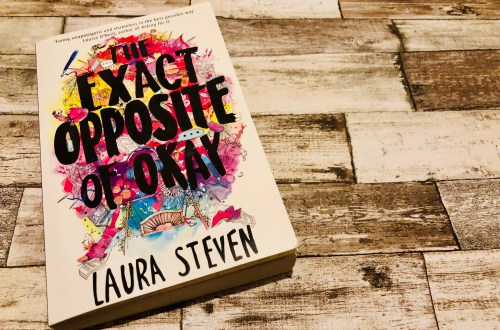The Exact Opposite of Okay by Laura Steven on a wooden background