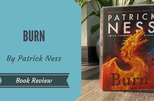 """Burn By Patrick Ness on a wooden table with a plant in the background. There is a blog graphic overlay on the image with the wording """"Burn by Patrick Ness Book Review"""""""