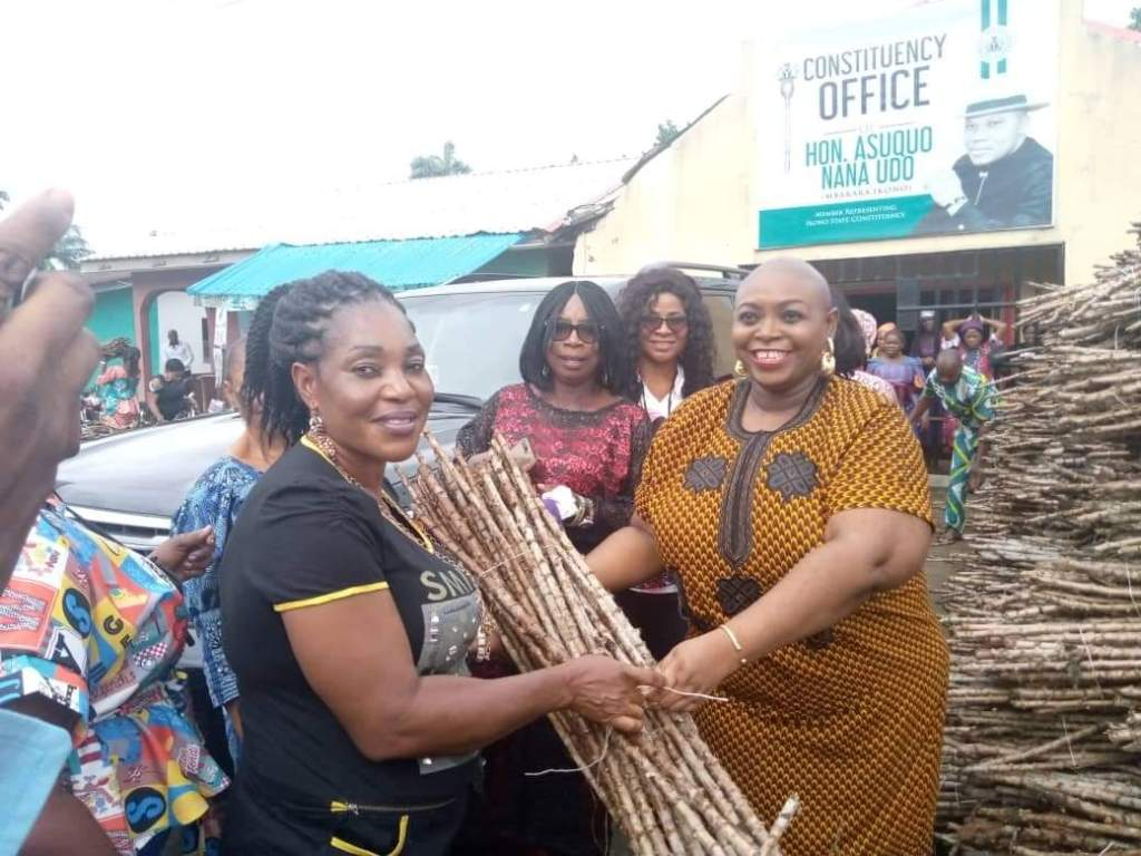 Wife of the Lawmaker presenting a bundle of cassava stems to one of the beneficiaries