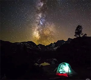 Lit tent on a mountain trial under a clear summer sky with lots of stars.