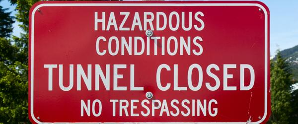 Photo of a sign that reads: Hazardous Conditions. Tunnel Closed. No Trespassing