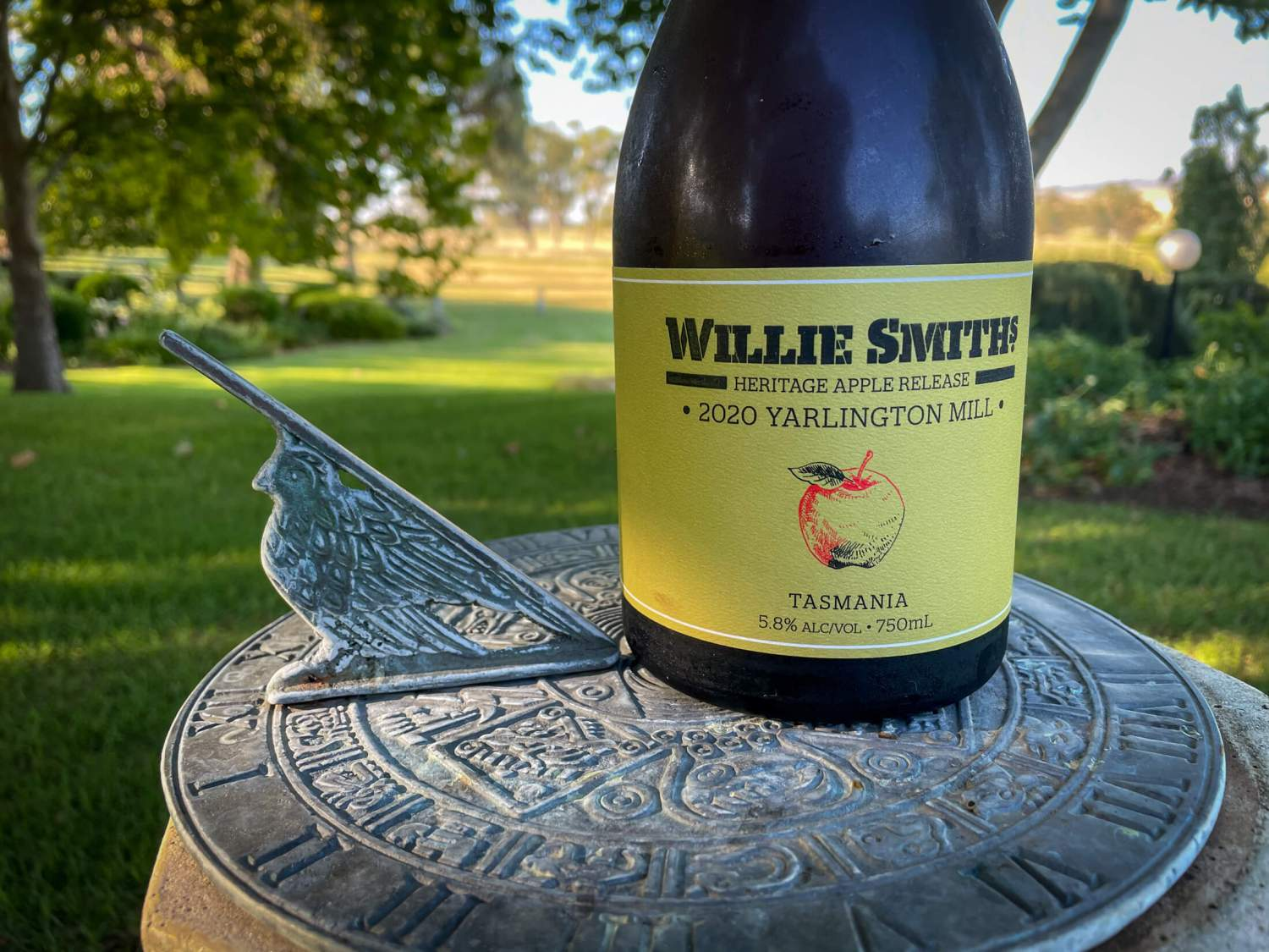 Willie Smiths 2020 Yarlington Mill Cider bottle on a sun dial in the a garden