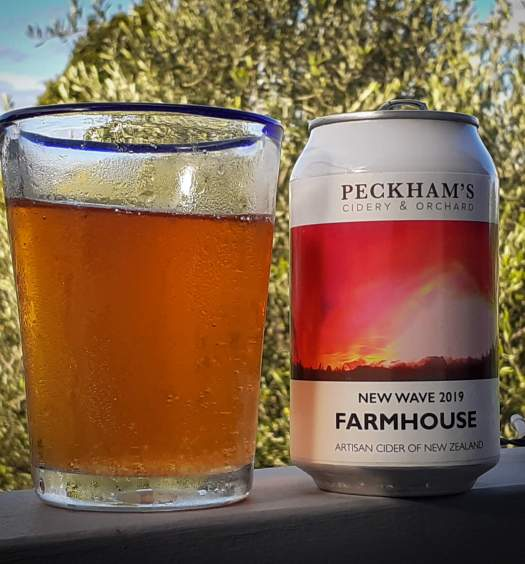 Peckhams Farmhouse Cider can and glass of the cider on a balcony