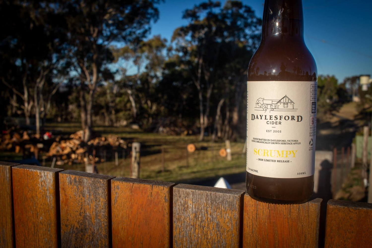 bottle of Daylesford Scumpy Cider 2020 sitting on a fence