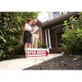 Real estate agent shows a board to a homebuyer next to an open house sign
