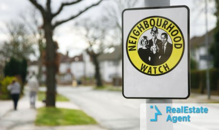 A neighborhood watch sign hangs on a pole in an empty street at daylight