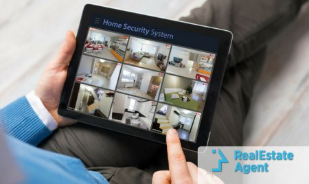 Close-up of a hand scrolling an iPad filled with smart house security systems