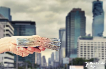 girl holding in her hand a pile of money and having skyscrapers in the background