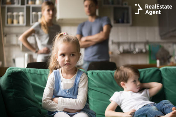 kids sitting upset on a couch while parent are in the background