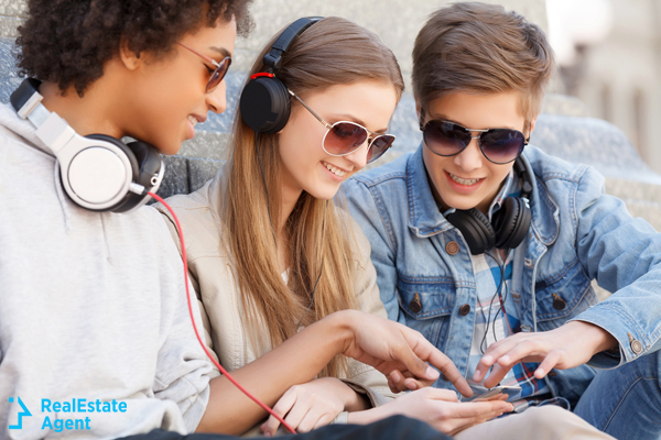 teenagers with headsets listening to music together