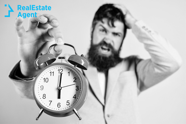 guy with beard holding an alarm clock in his hand