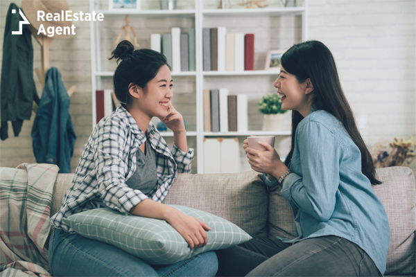 young roommate girls talking while sitting on a couch
