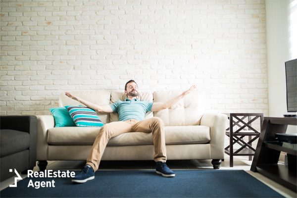 young guy enjoying the solitude of his room by relaxing on his couch