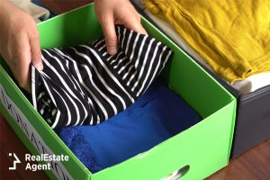Woman putting folded clothes in donation box