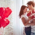 beautiful couple with gift and red balloons
