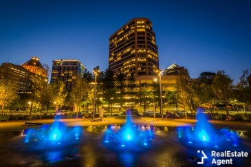 fountains and buildings at night in downtown greensboro