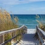 sandy boardwalk path to a snow white beach