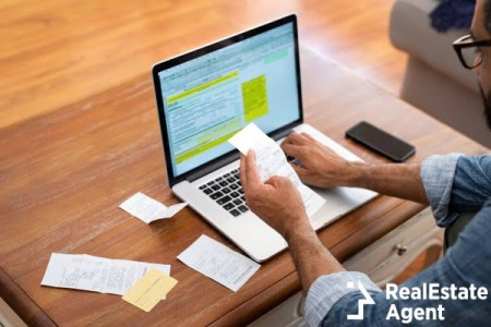 hands of businessman analyzing invoice on laptop