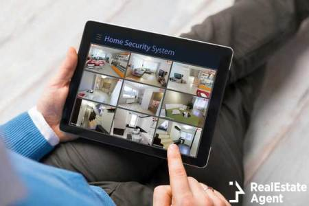 man looking at home security system on tablet