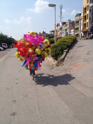 A balloon seller rides his bike in Hanoi
