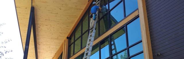 Chris on a ladder cleaning large windows in mancos co