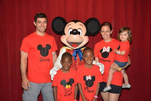 family in matching Disney shirts meeting Mickey at magic kingdom