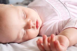 middle names for girls feature image of a sleeping baby in pink