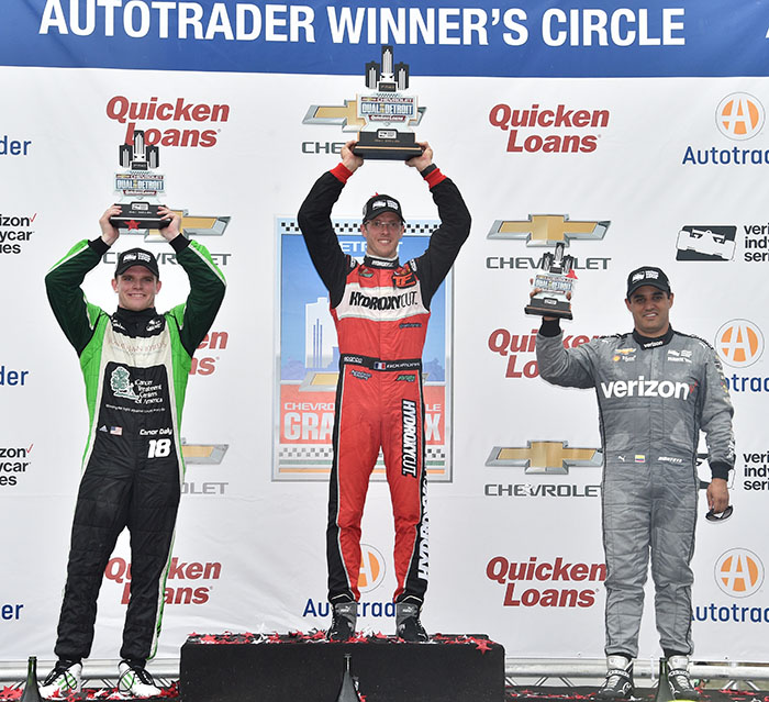 Sebastien Bourdais, Conor Daly, and Juan Pablo Montoya hoist their trophies on the Winner's Circle at Belle Isle Park following Race 1 of the Chevrolet Dual in Detroit