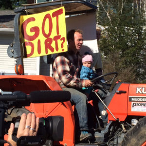 Pete Johnson on tractor with Got Dirt? sign at farm rally