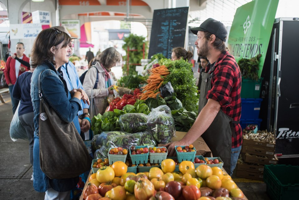 JM Fortier talks to customers at his market stand at the Jean-Talon Market in Montreal