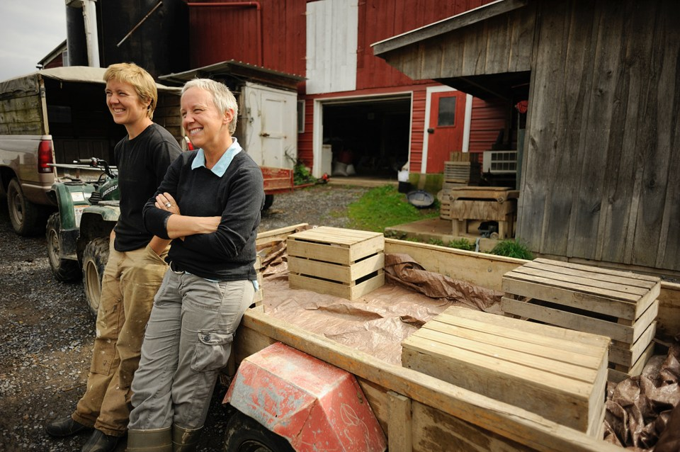 Debra Brubaker and Hannah Smith-Brubaker lean on lumber at Village Acres Farm in Mifflintown, Pennsylvania