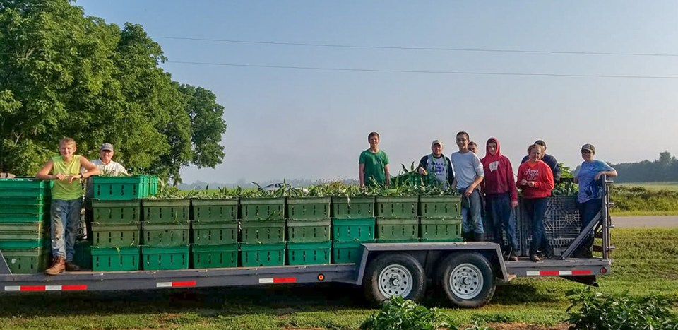 Team poses on flatbed trailer with corn harvest at Wheatfield Hills Wisconsin