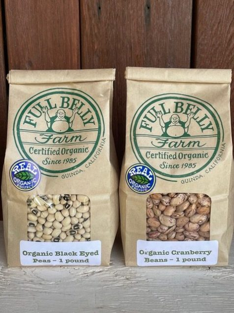"Two brown bags with clear windows showing black eyed peas and cranberry beans with label reading ""Full Belly Farm. Certified Organic since 1995. Guinda, California. Real Organic Project"""